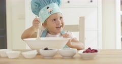 Adorable smiling toddler at mixing bowl Stock Footage