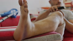 Man with injured ankle on sofa' Stock Footage