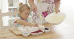 Little girl assisting Mum with the baking Stock Footage