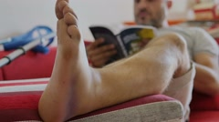 Man with injured ankle relaxing on sofa' Stock Footage