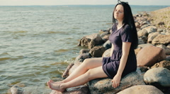 Girl sitting on rocks on the coast and posing Stock Footage
