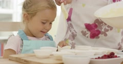 Happy little girl with empty muffin holders Stock Footage