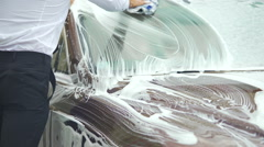 Squeamish driver washing car and shaking foam off hands, carwash service Stock Footage