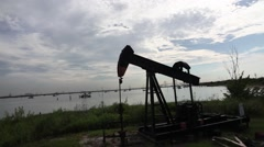 Oil pumps in front of a body of water silloutte Stock Footage