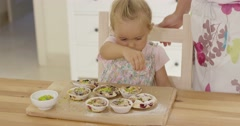 Close up on girl sprinkling toppings on muffins Stock Footage