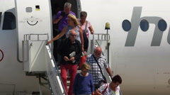 Passengers descend from a twin-turbofan airliner at Danube Delta airport Stock Footage
