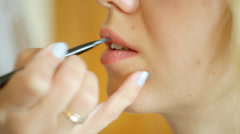 Professional makeup artist paints a model lips Stock Footage