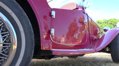 Vintage MG car in a collector's car exhibition - close up on wheel + panoramic Stock Footage