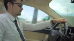 Handsome man in suit driving car to work, businessman turning steering wheel Stock Footage