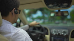 Businessman in suit and sunglasses behind steering wheel, driving car in city Stock Footage