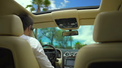 Driving in resort city on a sunny day, view on male driver from back seat of car Stock Footage