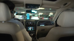 Businessman driving luxury car at parking lot in building, view from back seat Stock Footage