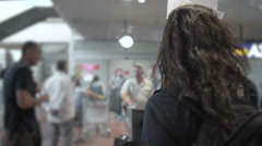 Female tourist guide standing in airport, waiting on guests, holding name sign Stock Footage