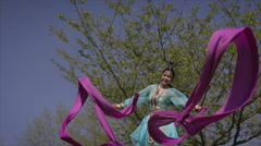 Chinese Ribbon Dancer performing in traditional costume outdoors Stock Footage