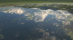 CLOSE UP: Amazing glassy lake water surface reflecting big puffy white clouds Stock Footage