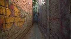 Narrow path between brick walls, moving camera forward Stock Footage