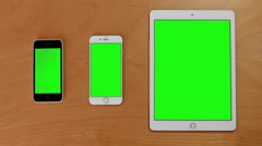 Top shot of hand touch phones and ipad on green screen - stock footage