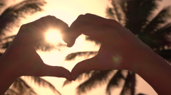 CLOSE UP: Making heart with hands over golden sun with lush palms in background Stock Footage