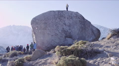 Man stands on top of boulder after sending the climb Stock Footage