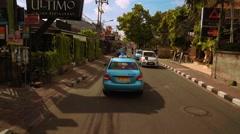 Following blue taxi on Seminyak street Stock Footage