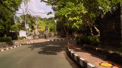 Bali street turning, moving past temple, backwards Stock Footage