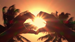 CLOSE UP: Making heart with hands over setting sun with lush palms in background Stock Footage