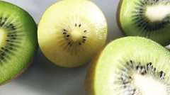 Kiwi fruits sliced in half on white background Stock Footage