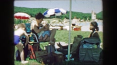 1957: Mother feeding baby at outdoor public swimming pool location. GLEN, NEW Stock Footage