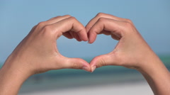 CLOSE UP: Making heart symbol with hands over blue cloudless sky and emerald sea Stock Footage