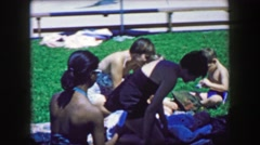 1957: Big multiracial family friends enjoying public pool summertime relaxation. Stock Footage