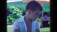 1957: Adorable boy kid holding paint brush explaining his artistic vision. GLEN, Stock Footage