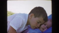 1957: Brother cuddling nuzzle against baby boy brother smushed face. GLEN, NEW Stock Footage