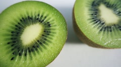 Kiwi fruits in row sliced in half on white background Stock Footage