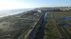 High aerial over an Amtrak train traveling beside the Pacific ocean near San Stock Footage