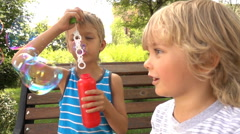 Little boys having fun with soap bubbles in the park Stock Footage