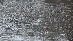 CLOSE UP: Amazing circular pattern created on puddle water surface by raindrops Stock Footage