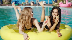 Two girls of swimsuit floating in the pool float. 20s. 1080p Slow Motion Stock Footage