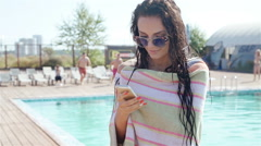 Portrait of beautiful girl taking a mobile phone at the swimming pool. 20s Stock Footage