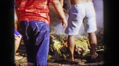 1958: Uncovering pig roast Hawaiian luau smoking pile of food. HONOLULU, HAWAII Stock Footage