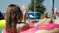 Portrait of a pretty young woman lying on deckchair with lollipop outdoors. 20s Stock Footage