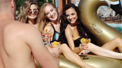 Slow motion sequence of friends having party in swimming pool drinking champagne - stock footage