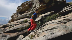 Kid climbing up the rock mountain Stock Footage