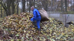 Worker man carry bag sack full of dry leaves and dump it on compost pile. 4K Stock Footage