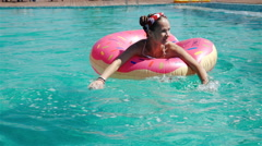 Low angle shot of blue swimming pool water and girl splashing while holding onto Stock Footage