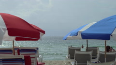 Blue and red umbrellas facing the pacific ocean, Miami Beach Stock Footage