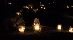 Flaming candles on the grave on All saints day at night. Focus change. 4K Stock Footage