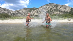 Kids running to the water in slow motion on summer holidays Stock Footage