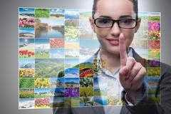 Businesswoman pressing virtual button on nature collage Kuvituskuvat