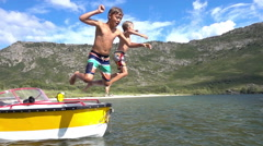 Boys jumping into water together in slow motion Stock Footage