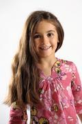Pretty vivacious little girl with long brown hair Stock Photos